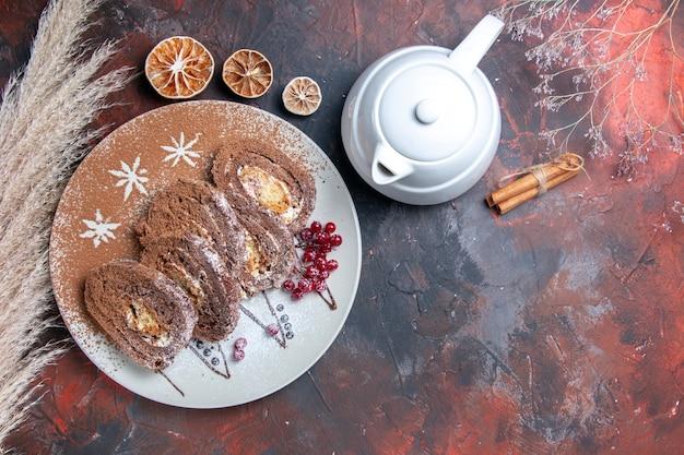 Vista dall'alto deliziosi rotoli di biscotti a fette torte cremose sul pavimento scuro