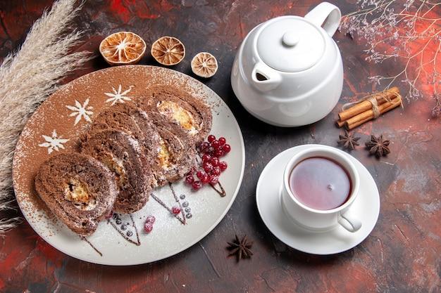 Vista dall'alto deliziosi rotoli di biscotti a fette di torte cremose su torte di torta da tavola scura dolci
