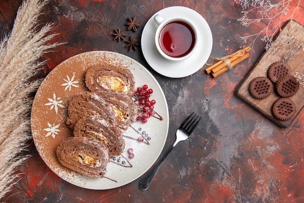 Vista dall'alto deliziosi rotoli di biscotti con biscotti su torte di torta dolce tavolo scuro