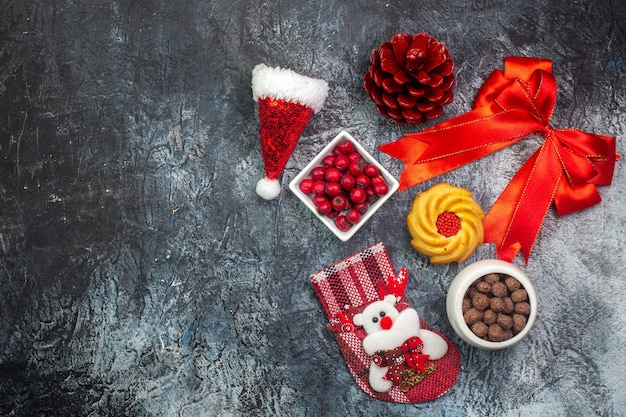 Top view of delicious biscuits and cornel chocolate in white pots new year sock red conifer cone red ribbon on the left side on dark surface