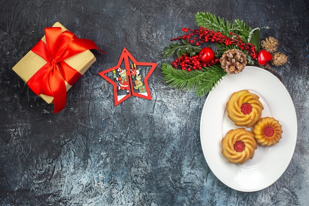 Top view of delicious biscuits on a white plate and new year decorations gift with red ribbon on dark surface