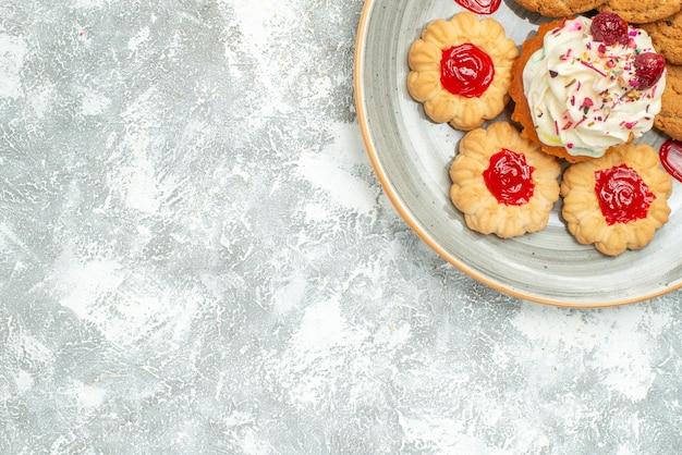 Вид сверху вкусного печенья с печеньем и кремовым пирогом на белом фоне сладкий чай бисквитное печенье сахарный пирог