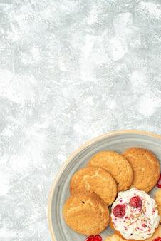 上面図白い背景の上のクッキーとクリームケーキとおいしいビスケット甘いお茶ビスケットクッキーシュガーケーキ