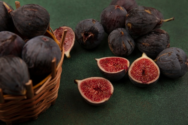 Top view of delicious black mission figs on a bucket with black figs isolated on a green wall