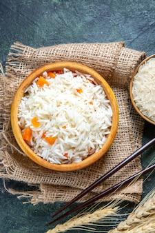 Вид сверху вкусный отварной рис с сырым рисом внутри маленькой тарелки на темном столе