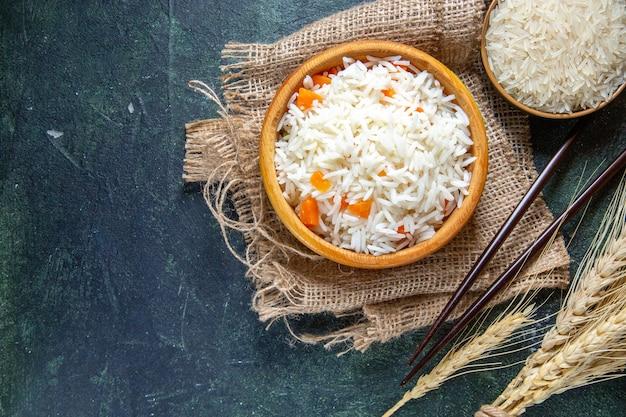 어두운 책상에 작은 접시 안에 원시 쌀과 상위 뷰 맛있는 삶은 쌀