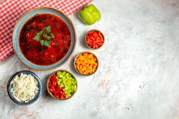 明るい白いスペースに肉とコショウを添えたトップビューのおいしいボルシチの有名なウクライナのビートスープ