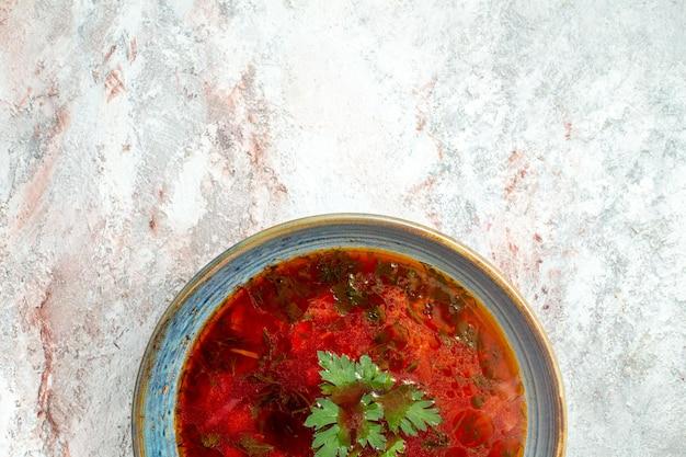 Vista dall'alto deliziosa zuppa di barbabietola ucraina famosa borsch con carne all'interno del piatto sulla scrivania bianca