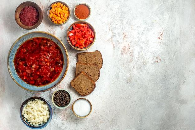 Вид сверху вкусный борщ украинский свекольный суп с хлебными буханками на белом пространстве