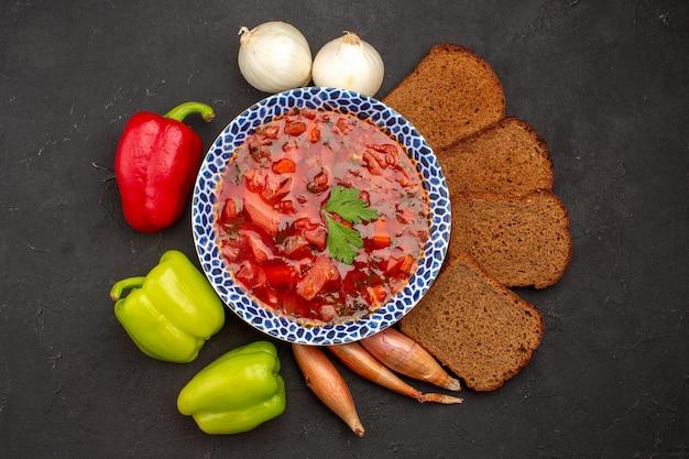 Вид сверху вкусного борща со свежими овощами и буханками хлеба на темном пространстве