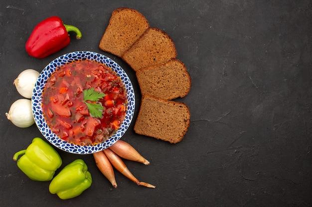 Vista dall'alto delizioso borsch con verdure fresche e pagnotte di pane nello spazio buio