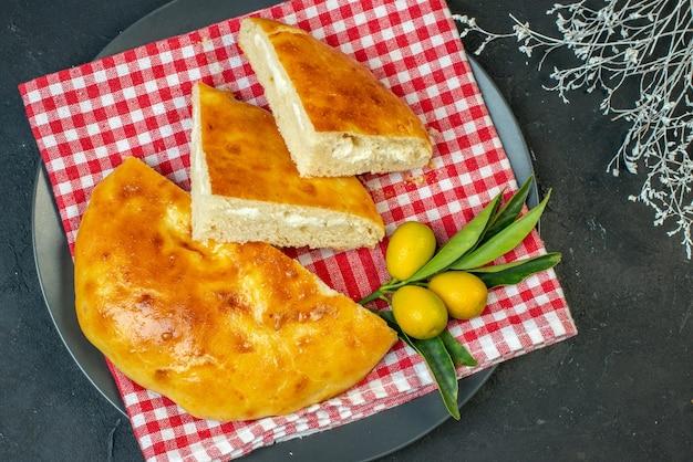 Vista dall'alto di deliziosi kumquat di pane con gambo su superficie scura