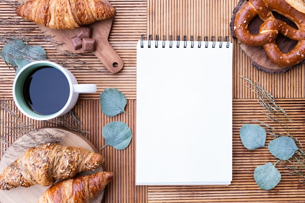 Top view of delicious breakfast with coffee and pastries, with copybook in the center
