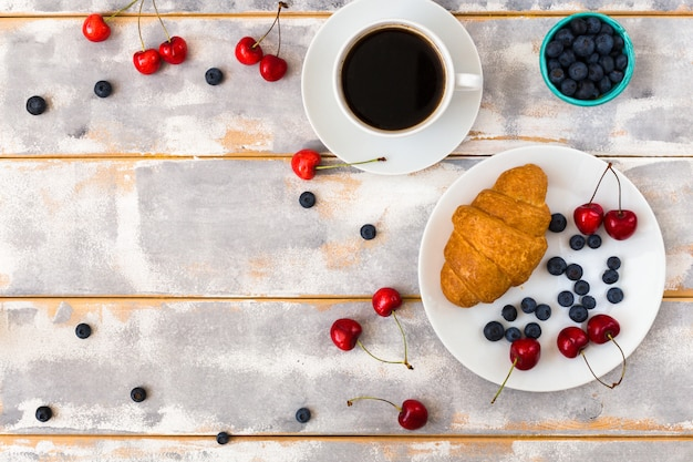 Top view of a delicious breakfast with croissants, coffee and blueberries and cherries on the table