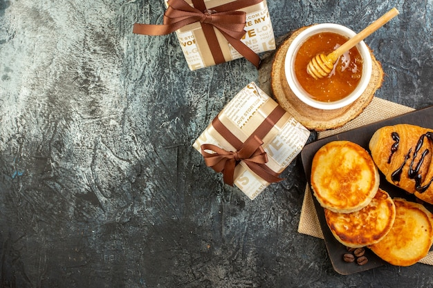 Top view of delicious breakfast with pancakes on wooden cutting board honey beautiful gift boxes on dark surface