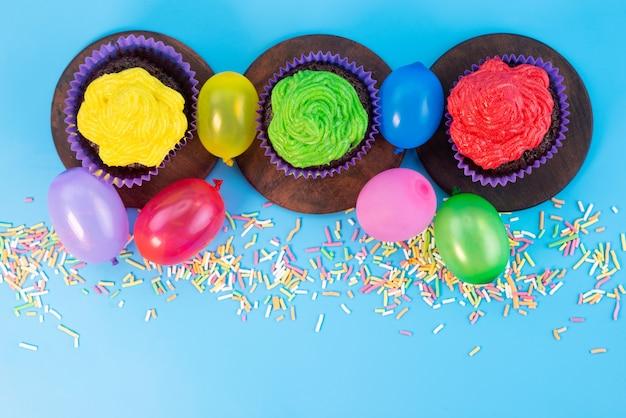 Una vista dall'alto deliziosi brownies all'interno di forme viola a base di cioccolato insieme a caramelle su blu, colore biscotto di caramelle