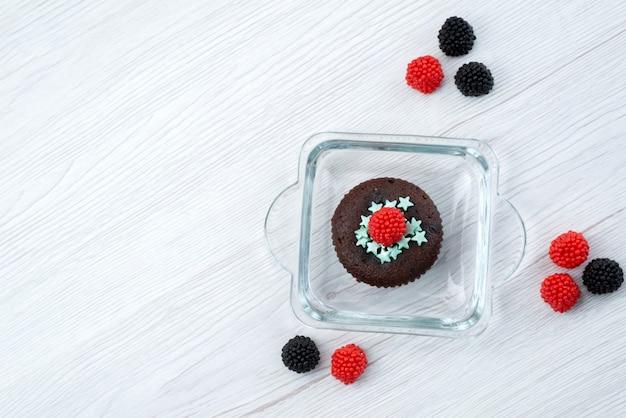 Una vista dall'alto delizioso browny all'interno della forma viola insieme a bacche fresche su dolci bianchi, color caramella