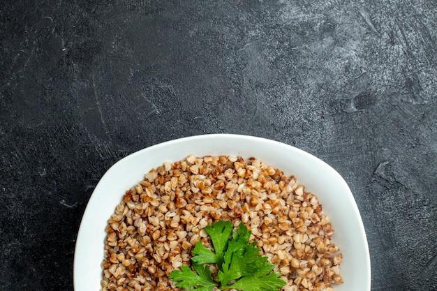 Vista dall'alto delizioso pasto di grano saraceno all'interno del piatto sulla scrivania grigia