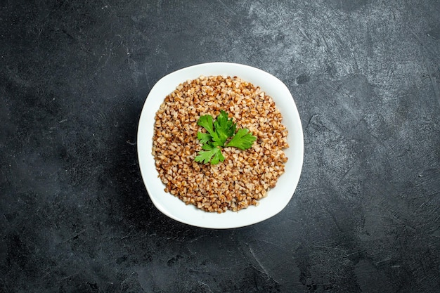 Top view delicious buckwheat meal inside plate on a grey space