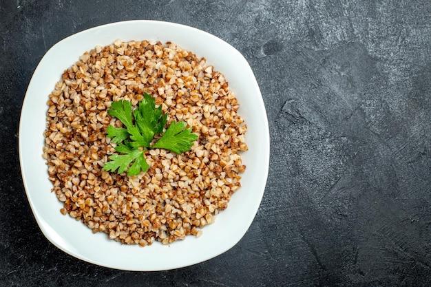 Vista dall'alto delizioso pasto di grano saraceno all'interno del piatto sullo spazio grigio