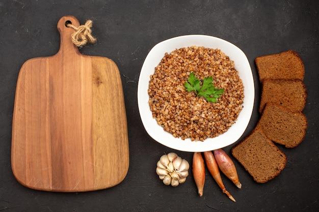 Vista dall'alto delizioso pasto di grano saraceno con pagnotte di pane scuro su spazio grigio