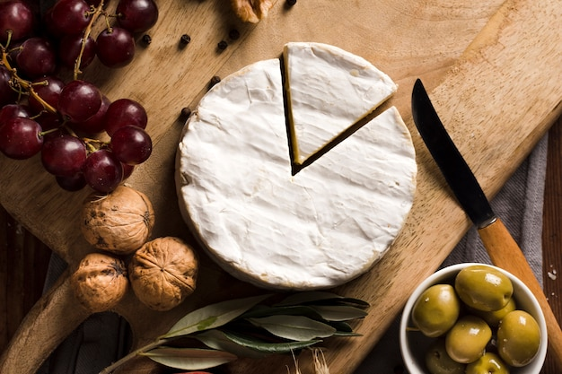 Top view delicious buffet with cheese on wooden board