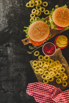 Top view of delicious burgers and fried onion rings