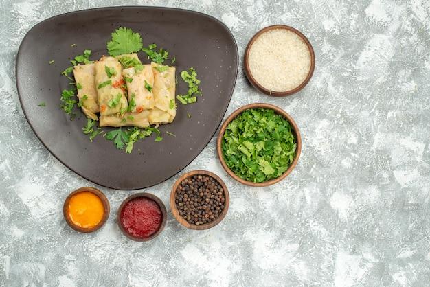 Вид сверху вкусной капустной долмы состоит из мясного фарша с зеленью на белом фоне, калорийное блюдо из мяса, ужина