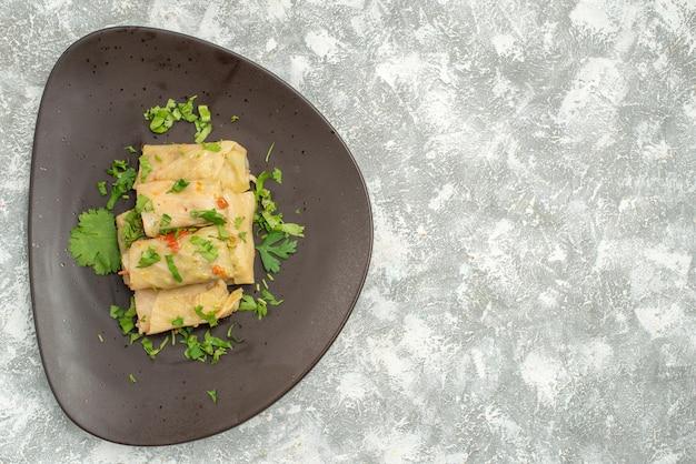 Вид сверху вкусная долма из капусты состоит из мясного фарша с зеленью на белом фоне мясо ужин калорийность масло блюдо еда