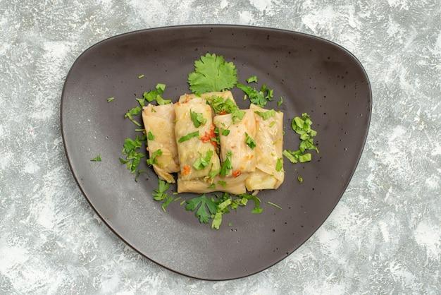 上面図おいしいキャベツドルマは、白い背景に緑のひき肉で構成されています肉ディナーカロリーオイル皿料理