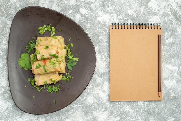 上面図おいしいキャベツドルマは、白い机の上の緑のひき肉で構成されています肉ディナーカロリーオイルディッシュフード