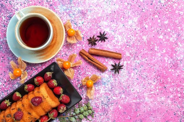 Вид сверху вкусный торт внутри черной формы для торта со свежей красной клубникой, корицей и чаем на розовом столе.