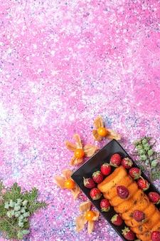 핑크 책상에 신선한 빨간 딸기와 검은 케이크 팬 안에 상위 뷰 맛있는 케이크.