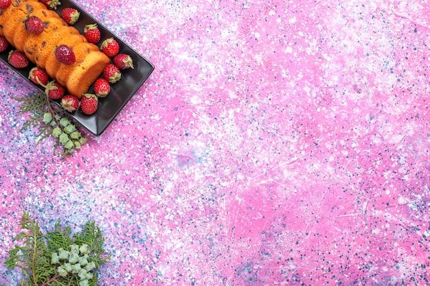 Vista dall'alto deliziosa torta all'interno di una tortiera nera con fragole rosse fresche sulla scrivania rosa.