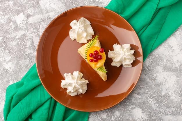 明るいデスクケーキビスケット甘い生地焼きにクリームと茶色のプレート内のアプリコットの平面図おいしいケーキのスライス