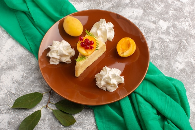 トップビューおいしいケーキスライスアプリコットスライスクリームとライトデスクケーキビスケットシュガー甘い生地焼きに茶色のプレート内の新鮮なアプリコット