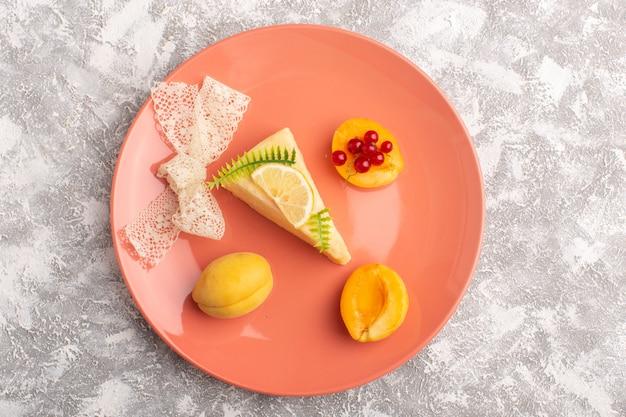 Vista dall'alto deliziosa fetta di torta con fetta di albicocche e albicocche fresche all'interno del piatto di pesche sulla scrivania leggera torta biscotto zucchero pasta dolce cuocere
