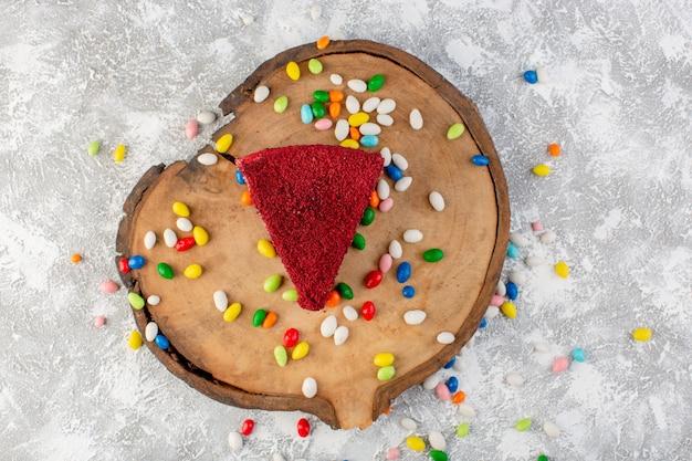 Вид сверху вкусный кусочек торта со сливками и фруктами на деревянном столе с разноцветными конфетами, бисквитными сладкими конфетами