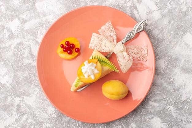 明るいデスクケーキ砂糖甘い焼き生地のピンクプレート内のクリームアプリコットと平面図おいしいケーキスライス