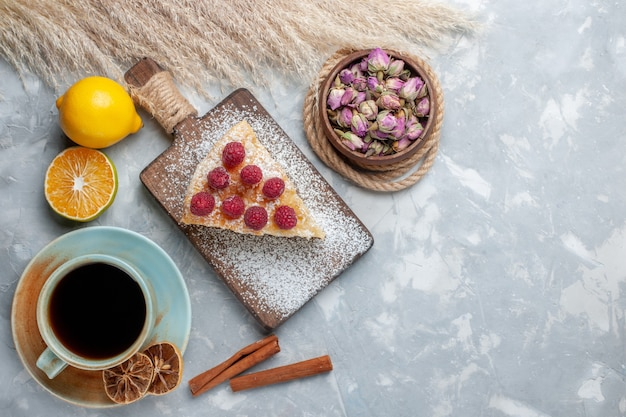 トップビューライトデスクケーキビスケットスイートシュガーベイクにお茶とレモンのカップとおいしいケーキスライス