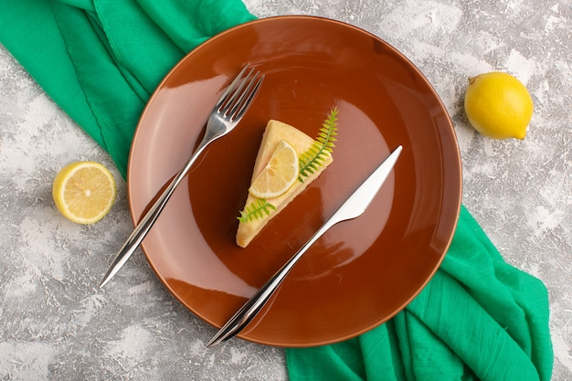 Вид сверху вкусный кусочек торта с лимоном внутри коричневой тарелки на светлом фоне с зеленой тканью, выпечкой из бисквитного теста