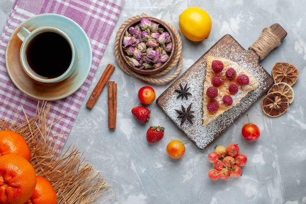 Вид сверху вкусный кусочек торта с лимонным чаем и фруктами на белом письменном столе, печенье, сладкая выпечка