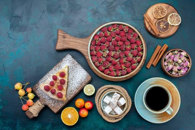Vista dall'alto deliziosa fetta di torta con tè lamponi e frutta sullo zucchero blu scuro della torta della torta della scrivania