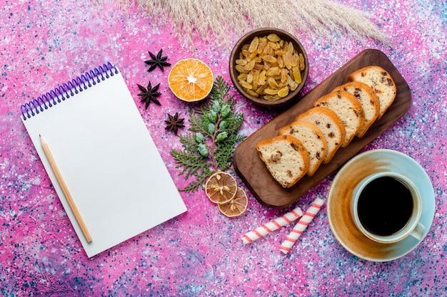 Vista dall'alto una deliziosa torta a fette di torta con uvetta e con una tazza di caffè sulla scrivania rosa chiaro cuocere la torta zucchero biscotto dolce biscotto