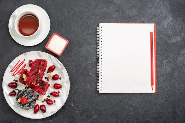 トップビューおいしいケーキは灰色の机の上にお茶とフルーティーなケーキをスライスします