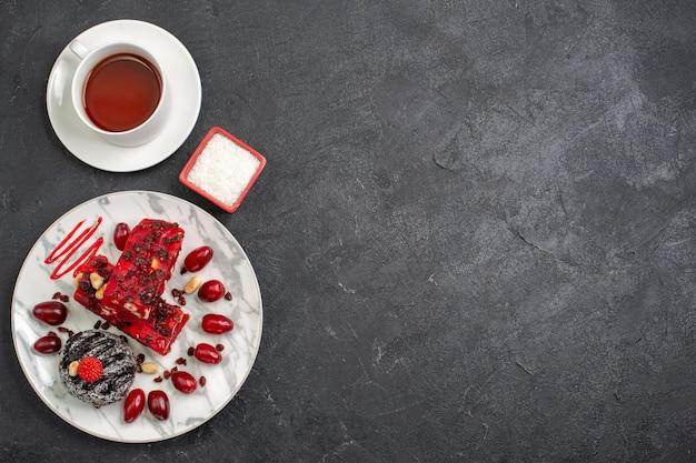 Вид сверху вкусные кусочки торта, фруктовый торт с чашкой чая на сером пространстве