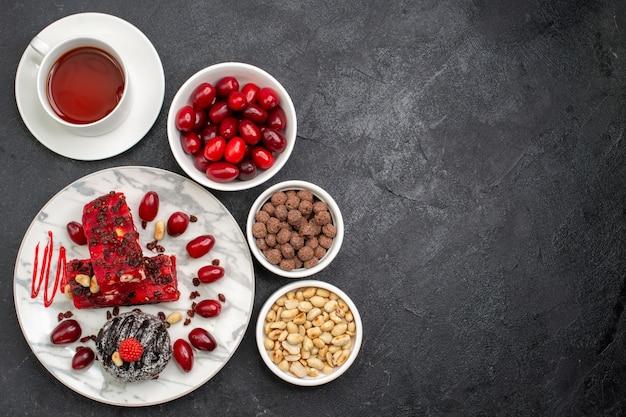 トップビューおいしいケーキは、灰色のスペースにナッツとお茶とフルーティーなケーキをスライスします