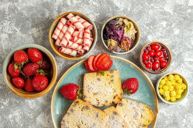 Vista dall'alto deliziose fette di torta con frutta e caramelle sulla torta dolce superficie leggera