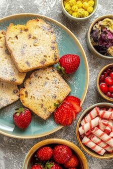 Vista dall'alto deliziose fette di torta con frutta sulla torta di frutta torta dolce superficie leggera