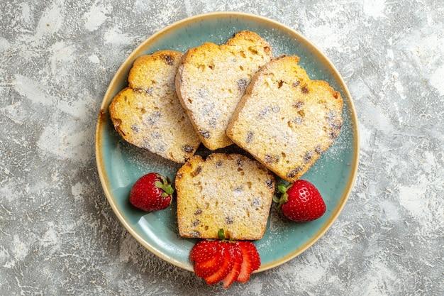 Вид сверху вкусные кусочки торта с фруктами на светлой поверхности фруктовый торт сладкий пирог